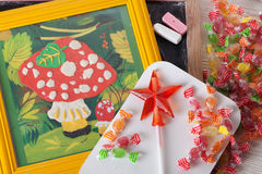 Children's drawing plasticine mushroom amanita autumn still life on a table board crayons candy lollipop Stock Photo