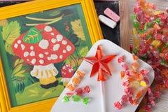 Children's drawing plasticine mushroom amanita autumn still life on a table board crayons candy lollipop Stock Photo