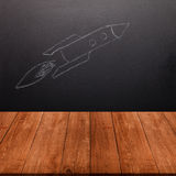 Children's drawing a rocket on a chalkboard behind a wooden tabl Stock Photos