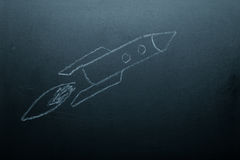 Children's drawing a rocket on a chalkboard. Toned Stock Images