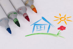 Children s drawing. Some markers lie in children s drawing with the image of  house and sun. Photo taken on: January 19th, 2014 Stock Photos