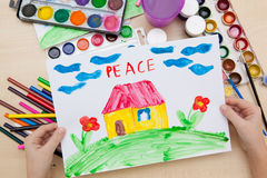 Children`s drawing watercolor. A child holding a watercolor drawing on paper with the word peace Royalty Free Stock Photography