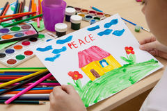 Children`s drawing watercolor. The child looks at a watercolor on paper of the peace Stock Photography