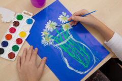 Children`s drawing watercolor. The child paints a watercolor bouquet of flowers on a blue background Stock Photos