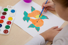 Children`s drawing watercolor. A child paints with watercolors on paper fruit Stock Photos