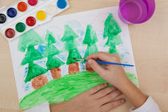 Children`s drawing watercolor. A child paints with watercolors on paper green coniferous forest Stock Images