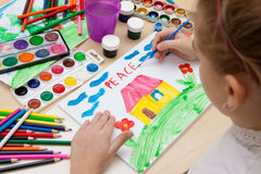Children`s drawing watercolor. A child paints with watercolors on paper drawing of the peace Royalty Free Stock Images