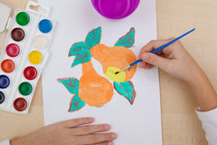 Children`s drawing watercolor. A child paints with watercolors on paper pears Royalty Free Stock Image