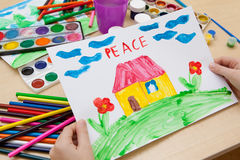 Children`s drawing watercolor. The child shows watercolor drawing on paper with the word peace Stock Image