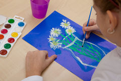 Children`s drawing watercolor. Girl paints a watercolor bouquet of flowers on a blue background Stock Images