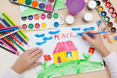 Children`s drawing watercolor. A kinder paints with watercolors on paper drawing of the peace Royalty Free Stock Image