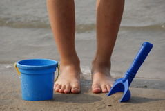 Children's feet with beach toys. The child is going to play sand with a shovel and a bucket Royalty Free Stock Photos
