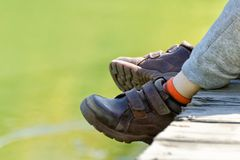 Children`s feet in brown leather shoes over the water Royalty Free Stock Image