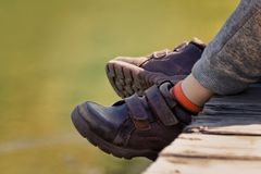Children`s feet in brown leather shoes over the water. Children`s feet in brown leather shoes over the water Stock Image