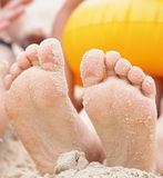 Children`s feet are buried in sand. Happy holiday on th e sea coast. Children`s feet are buried in sand. Games on the beach Royalty Free Stock Photos