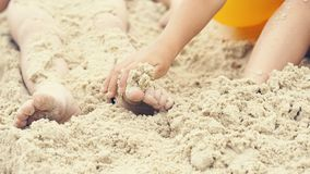 Children`s feet are buried in sand. Happy holiday on th e sea coast. Children`s feet are buried in sand. Games on the beach Royalty Free Stock Images