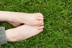 Children`s feet on the green grass - picnic Royalty Free Stock Images