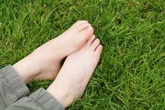 Children`s feet on the green grass - picnic Stock Image