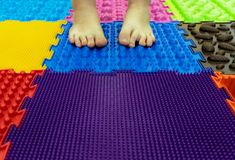 Baby Feet on a Special Orthopedic Carpet. Background. Children`s Feet on the Orthopedic Carpet. Prevention of Flatfoot royalty free stock photos