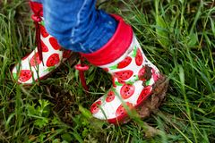 Children& x27;s feet in rubber boots royalty free stock images