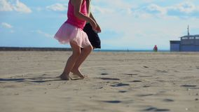 Children`s feet on the sand. Children`s feet run on the sand on the beach, hold hands, slow motion stock video