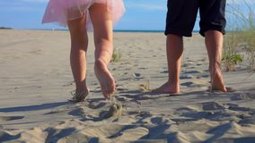 Children`s feet on the sand. Children`s feet are running along the sand to the sea, holding hands, slow motion stock footage