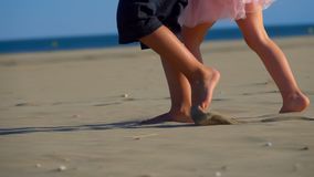 Children's feet on the sand. Children's feet are running along the sand to the sea, holding hands, slow motion stock video