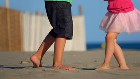 Children`s feet on the sand. Happy little boy and girl play on sand at beach stock footage