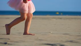 Children`s feet on the sand. Children`s legs running on the sand, slow motion stock video