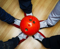 Children`s feet in shoes and a bowling ball Stock Photos