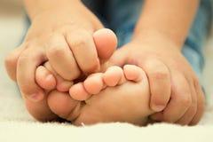 Children's feet. Small child hands firmly holding bare feet Stock Photo