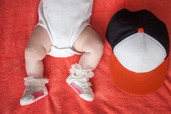Children's feet in sport shoes and hat on orange background. Children's feet wearing in sport shoes and cap on orange blanket background stock photography