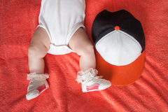 Children's feet in sport shoes and hat on orange background. Children's feet wearing in sport shoes and cap on orange blanket background Royalty Free Stock Photo
