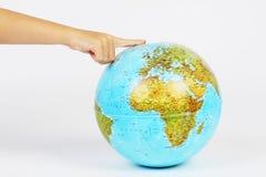 Children's finger on globe Stock Photo