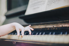 Children`s fingers on the keys of a piano playing. Stock Photography