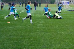 Children`s Football Team on the Pitch. Children`s football training ground. Young Soccer Players Running After the Ball. Ball soccer in kid football players stock photos