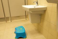 Children`s footrest near the sink in a public toilet. Concept - barrier-free environment royalty free stock image