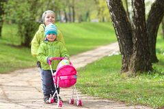 Children`s friendship. Small friends. Children walk in green park. Little boy and girl with toy carriage for doll stock photography