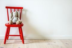 Children`s Furniture. Small red wooden chair with stuffed bunny stock photography