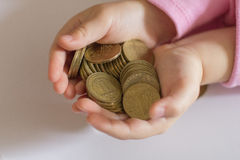 Children's future. Coins hold a baby in their arms Stock Image