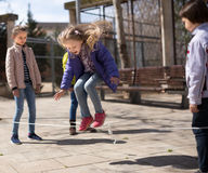 Children`s games. blonde Girl jumps over the rope Stock Images