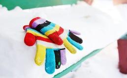 Children& x27; s gestrickte Handschuhe auf dem Schnee Stockbilder