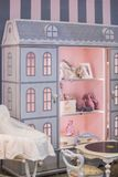 A children`s girl`s cute cupboard with shelves in the form of a doll`s house. Interior of a children`s room for a little princ stock photos