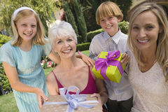 Children's Giving Gifts To Grandmother. Portrait of children's giving gifts to grand mother on birthday at lawn Stock Photos