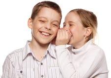 Children's gossip. Girl whispers boy in the ear secret. Childrens gossip royalty free stock images