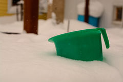 Children`s green bucket, which was filled with snow in the yard. Old children`s green bucket, which was filled with snow in the yard Stock Images