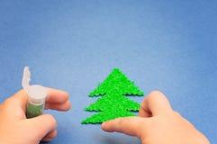 Children& x27; s-Hände, die mit Funkeln Weihnachtsbaum besprüht wurden, schnitten vom Plüsch auf Hintergrund des blauen Papiers h Stockfotos