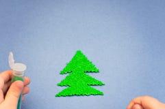 Children& x27; s-Hände, die mit Funkeln Weihnachtsbaum besprüht wurden, schnitten vom Plüsch auf Hintergrund des blauen Papiers h Lizenzfreies Stockfoto