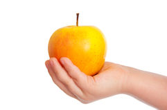 Children's hand with an apple. Royalty Free Stock Image
