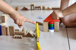 Children's hand and building block. Two kids is playing building block, one child is point at a yellow brick, the other is holding red triangel brick Stock Images
